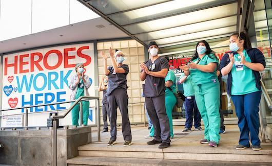 "Signs for ""Heroes work here"" outside healthcare facilities and even the homes of clinicians have popped up across the country. This photo shows healthcare workers at the Lenox Health emergency room entrance being greeted to cheers and thanks for their essential service during the COVID-19 pandemic in New York City at a public thank you event May 21, 2020."