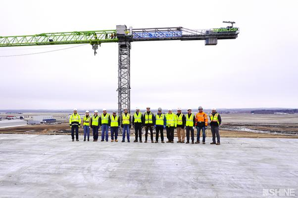 Shine executives are joined by the company's construction managers and partners at its medical isotope production facility. The group was commemorating the facility's achievement of weathertight status