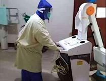 A radiology technologist using a rain coat and home-made face shield personal protective equipment (PPE) due to a severe shortage of PPE at Sen. Gerardo M. Roxas Memorial District Hospital in Iloilo City, Philippine. The techs used spoiled X-ray film with the emulsion stripped off, foam packing material, elastic and a glue gun to make their own face shields. Photo by Dodge Moises, radiology technologist.