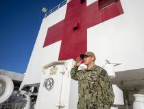 Lt. Ronald Silver, from Ontario, Calif., renders a hand salute during morning colors aboard the hospital ship USNS Mercy in the Port of Los Angeles to help with local efforts to contain and treat COVID-19 patients. U.S. Navy photo by Mass Communication Specialist 2nd Class Abigayle Lutz.